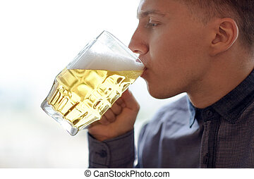 close up of young man drinking beer from glass mug - people,...