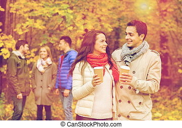 group of smiling friend with coffee cups in park - love,...