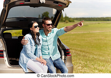 happy couple hugging at open hatchback car trunk - travel,...