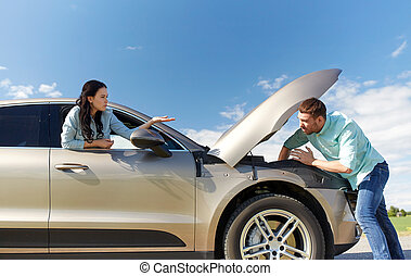 couple with open hood of broken car at countryside - road...