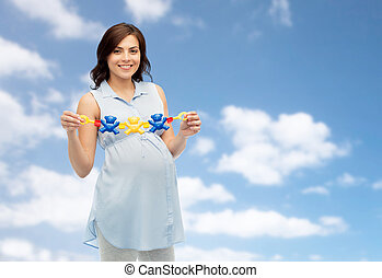 happy pregnant woman holding rattle toy - pregnancy,...