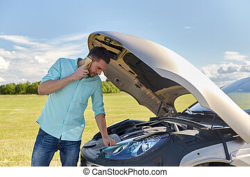 man with broken car calling on smartphone - road trip,...