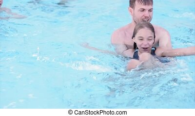 Happy family enjoying in pool - Happy little girl learning...