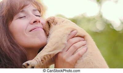 Woman kisses a puppy