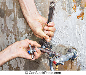 Dismantling of old faulty faucet, hands of plumber with wrench.