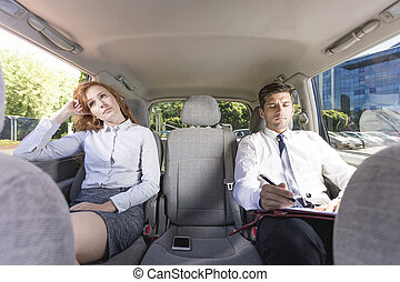 It's gonna be a long drive... - Business couple sitting on a...