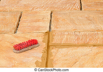 Laying concrete outdoor tiles sandstone colored on terrace and scrubbing brush