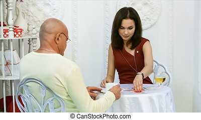 Girl gives a deck of cards to the man