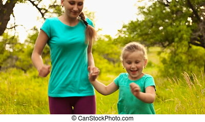 Mom and daughter running in summer park