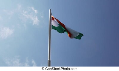 Textile flag of India on a flagpole in front of blue sky