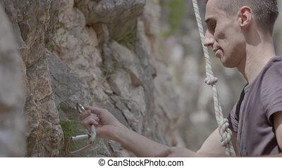 A male rock climber climbs up a rock