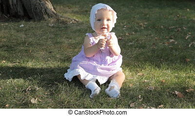 A baby girl in a bonnet sitting on the grass lit by setting...