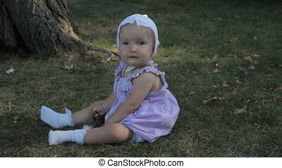 A baby girl in a bonnet sitting on the grass and tears it....