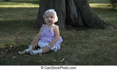 A baby girl in a bonnet sitting on the grass and holding a...