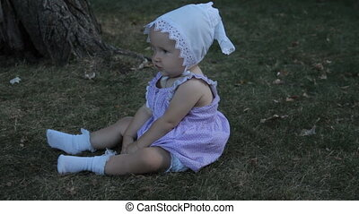 A baby girl in a bonnet sitting on the grass in a park