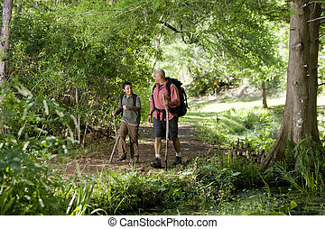 Hispanic father and son hiking on trail in woods - Father...