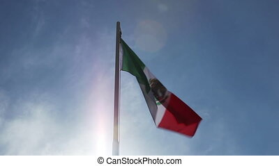 National flag of Mexico on a flagpole in front of blue sky