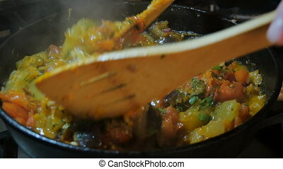In a saucepan, stirring with a wooden spoon vegetable stew,...