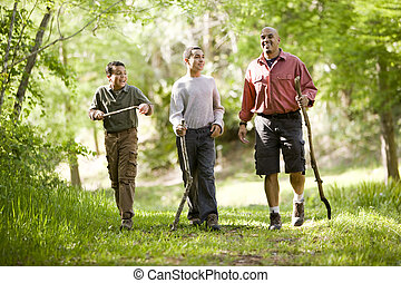 Hispanic father and sons hiking on trail in woods - Father...