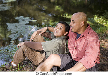 Portrait Hispanic father and son outdoors by pond having...
