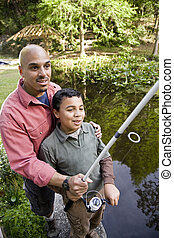 Hispanic father and son fishing in pond - Hispanic father...