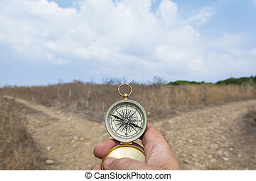 Which road? - Man holding a compass on a fork in the road on...