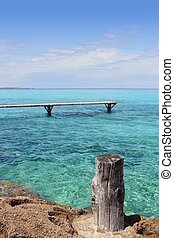 Formentera Illetes turquoise sea wooden pier aged trunk...