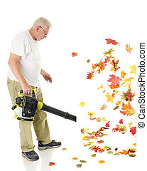 Blowing Leaves - A senior man blowing autumn leaves with his...