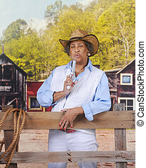 Woman Blowing Smoke - A mature African American Cowgirl in...