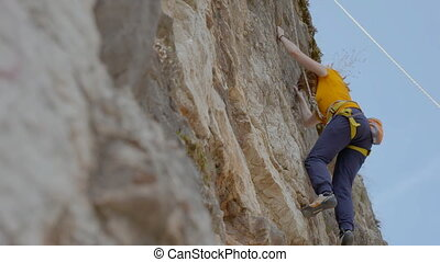 A female rock climber climbs up a rock