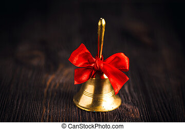 Antique brass hand bell with a red bow on a dark wooden...