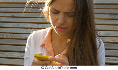 Young beautiful girl writes SMS on your smartphone. Reads...