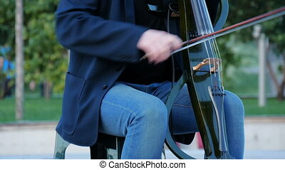 A street musician plays electric cello. In the summer in the...