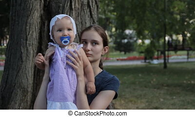 A very young nanny having a baby girl with a soother in her...