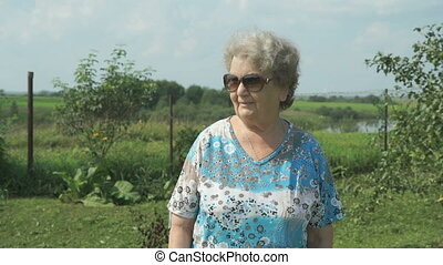 Old woman walking in the park of garden