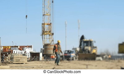 Builder goes to the background construction site