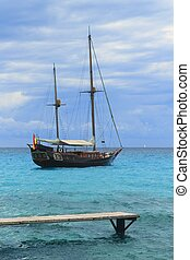 pirates inspired wood sailboat anchored turquoise sea...