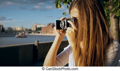 Attractive girl photographed retro camera.
