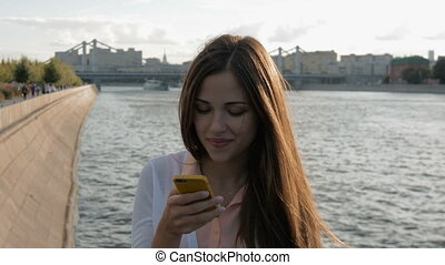 Young beautiful girl writes SMS on your smartphone. Sitting...