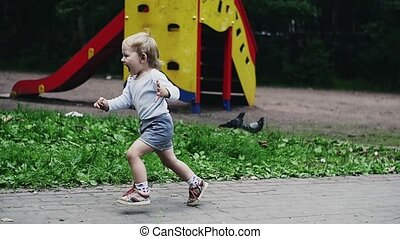 Little boy in shorts run to doves. Birds fly away. Summer park. Happiness.