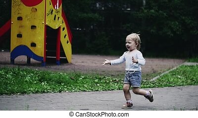 Blonde little boy run on playground to mother. Doves in summer park. Childhood