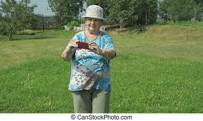 Elderly woman taking photos the nature of park using a...