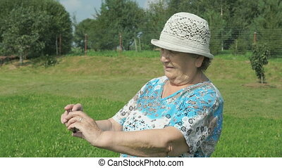 Old woman photographing the landscape of park - The old...
