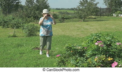 Aged woman taking photos the nature of park using a mobile...