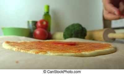Man putting tomato slices over pizza base. Cooking, part of...