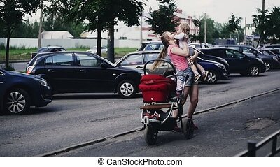 Mother hold little son on hands on street. Family. Summer....