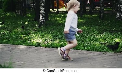 Blonde little boy running on playground in summer park for dove. Childhood. Sun