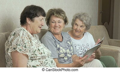 Elderly women look at photos on screen of tablets