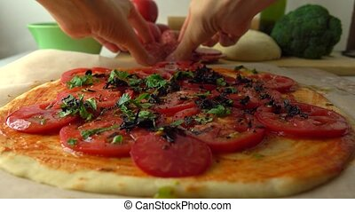 Man putting salami slices on homemade pizza. Cooking, part...