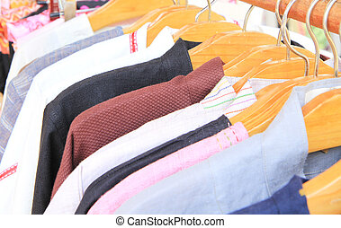 Close-up image of different shirts on wooden hangers